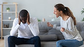 Unhappy African American couple quarreling, fighting at home