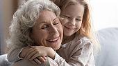 Little granddaughter embrace senior grandmother showing love