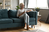 Calm mature woman relax on couch drinking tea