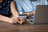 Crop of ethnic couple pay online with credit card