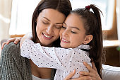 Close up smiling mother and adorable daughter hugging
