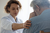 Female doctor touching shoulder comforting upset senior patient, closeup