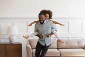 African father piggybacking little daughter playing together in living room
