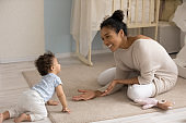 Happy biracial mom paly with baby toddler at home