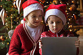 Happy children play on tablet on holidays at home