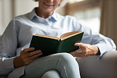 Close up of elderly female holding paper book in hands