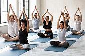 Seven multi-ethnic people meditating seated in lotus pose