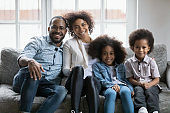 African family with little kids sitting on couch at home
