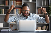 Happy african guy looking at pc screen scream with joy