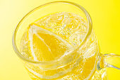 Highball Laced With Lemon juice Flavour. Yellow background.