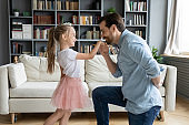 Dad holds hand kisses arm of little daughter at home