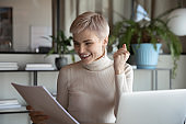 Businesswoman holding letter with unexpected fantastic news feels happy