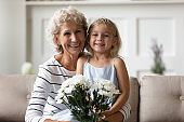 Cute little granddaughter greeting granny with anniversary
