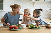 Caring daughters feeding mommy with vegetables