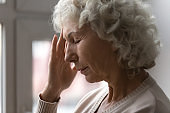 Unhappy elderly woman yearning alone at home