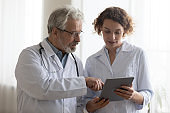 Medical team of two professional doctors talking using digital tablet
