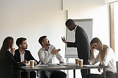 Multiracial colleagues argue at company meeting in office