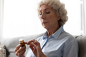 Senior woman holding glass bottle reads pills instruction