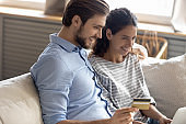 Happy young family couple involved in internet shopping at home.
