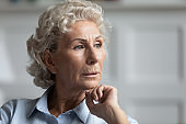 Thoughtful mature woman look in distance feeling lonely
