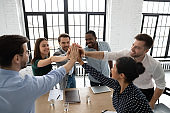 Excited diverse colleagues give high five celebrate success