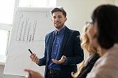 Successful male tutor make flip chart presentation at meeting