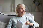 Happy mature woman distracted from reading book at home