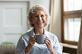Portrait of happy mature woman drink warm tea at home