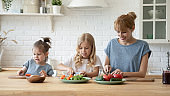 Cheerful young mother and children cooking salad together