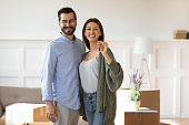 Portrait of happy couple show house keys moving together