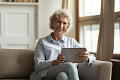 Portrait of smiling mature woman using modern tablet