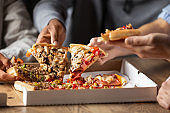 Close up of multiethnic friends share delicious pizza