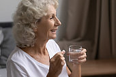 Close up smiling mature woman taking medication, holding round pill
