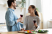 Young loving couple having fun in kitchen, drinking wine