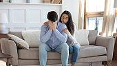 Young woman hug comfort upset husband at home