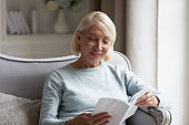 Middle-aged mature woman reading interesting book at home