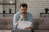 Pensive Caucasian man work on laptop reading paper documents