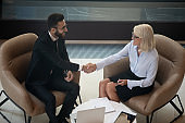 Smiling diverse businesspeople shake hands get acquainted at meeting