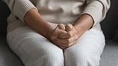 Close up of elderly woman join hands feel anxious