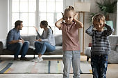 Unhappy little kids covering ears, suffering from parents argument