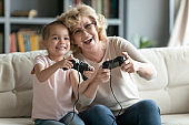 Grandmother and little granddaughter playing playstation at home