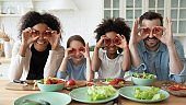 Family cooking together having fun covering eyes with red paprika
