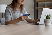 Happy young woman entering payment information, shopping online.