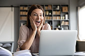 Excited surprised woman looking at laptop screen, reading news