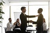 Caucasian businessman handshake greeting biracial male employee