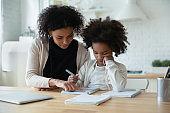 African mother helps with task to little schoolgirl daughter