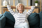 Peaceful calm older woman leaning back on couch