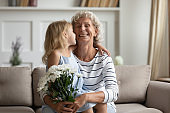 Little granddaughter congratulates granny with Women Day gave her flowers