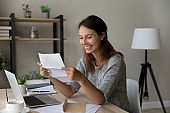 Smiling millennial woman reading letter with good news.