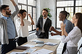 Excited diverse employees celebrating great teamwork result at meeting